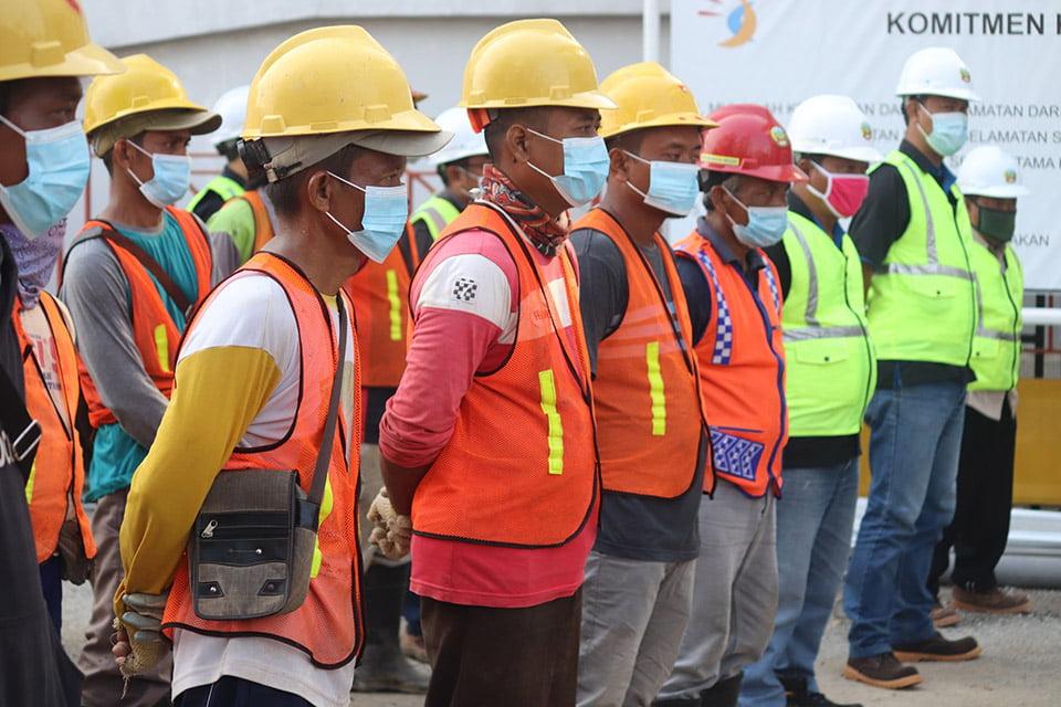 Pekerja konstruksi bangunan menggunakan rompi keselamatan kerja